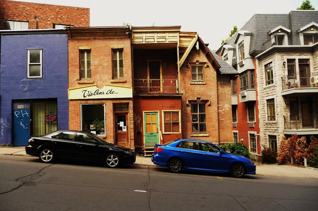 Современные авто на фоне старых домов Монреаля
